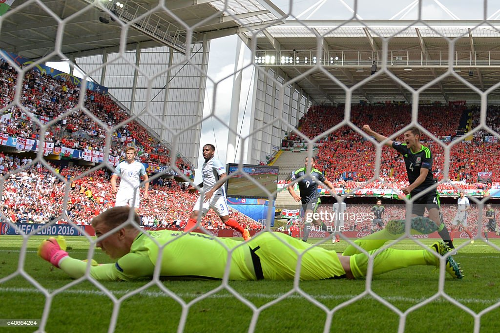 Wales' players celebrate after England's goalkeeper Joe Hart (front) reacts after the opening score by Wales' forward Gareth Bale (not pictured) during the Euro 2016 group B football match between England and Wales at the Bollaert-Delelis stadium in Lens on June 16, 2016. / AFP / PAUL