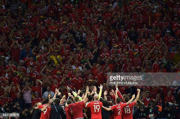 Wales' players celebrate at the end of the Euro 2016 quarter-final football match between Wales and Belgium at the Pierre-Mauroy stadium in...