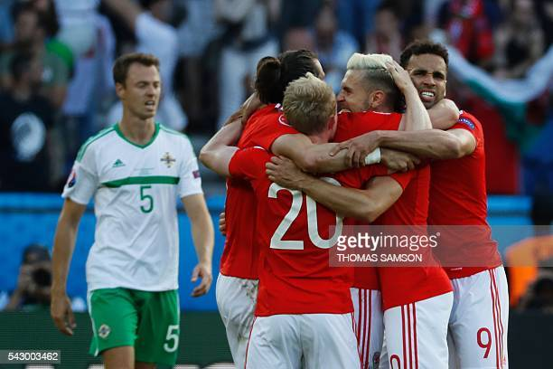 Wales' players celebrate their victory during the Euro 2016 round of sixteen football match Wales vs Northern Ireland, on June 25, 2016 at the Parc...