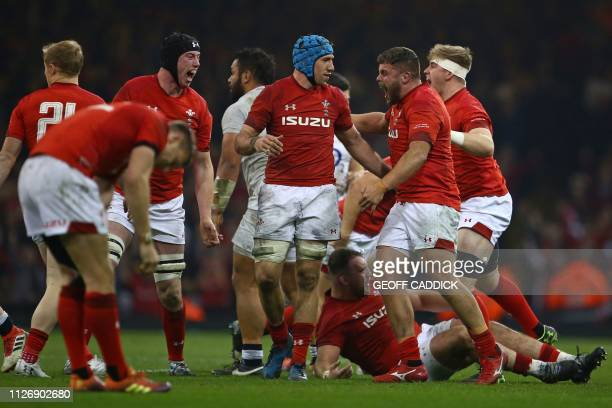 Wales' players celebrate their win on the pitch after the Six Nations international rugby union match between Wales and England at the Principality...
