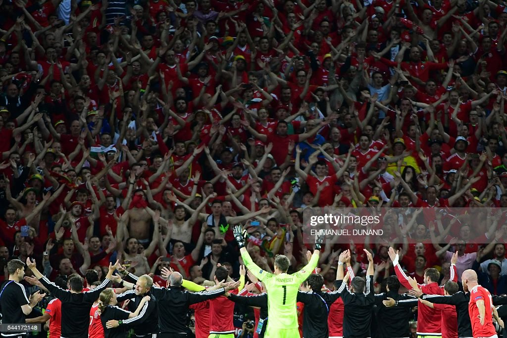 TOPSHOT - Wales' players celebrate with supporters after the Euro 2016 quarter-final football match between Wales and Belgium at the Pierre-Mauroy stadium in Villeneuve-d'Ascq near Lille, on July 1, 2016. Wales won the match 3-1. / AFP / EMMANUEL