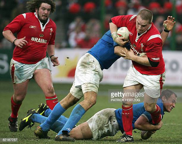 Wales' prop Gethin Jenkins is tackled by Italy's No.8 Sergio Parisse as teammate prop Adam Jones looks on during the VI nations rugby union match...