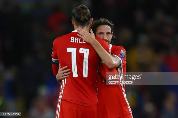 Wales' striker Gareth Bale and Wales' midfielder Joe Allen embrace on the pitch after the Euro 2020 football qualification match between Wales and...