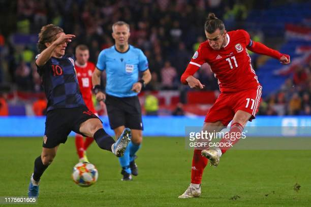 Wales' striker Gareth Bale has an unsuccessful shot under pressure from Croatia's midfielder Luka Modric during the Euro 2020 football qualification...