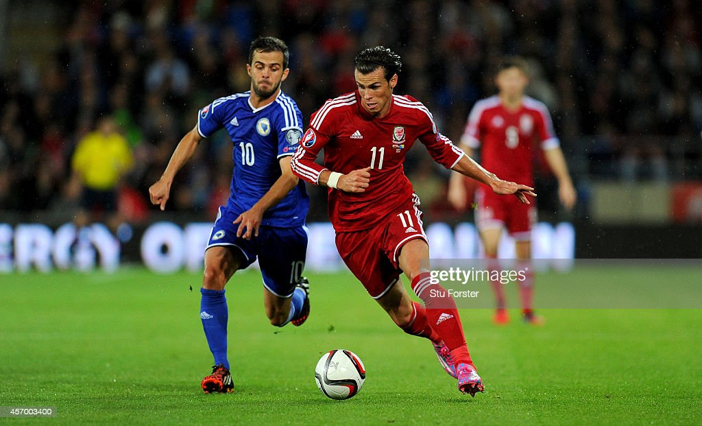 Wales striker Gareth Bale (r) races past Bosnia player Miralem Pjanic during the EURO 2016 Qualifier match between Wales and Bosnia and Herzegovina at Cardiff City Stadium on October 10, 2014 in Cardiff, Wales.