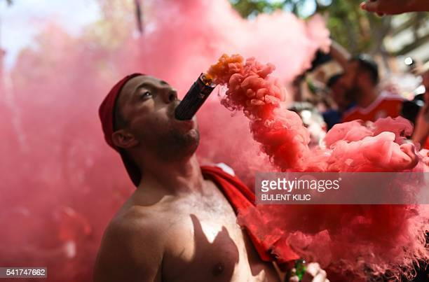 Wales' supporter cheers with a flare in his mouth downtown Toulouse southern France on June 20 2016 before the Euro 2016 football match of Russia vs...