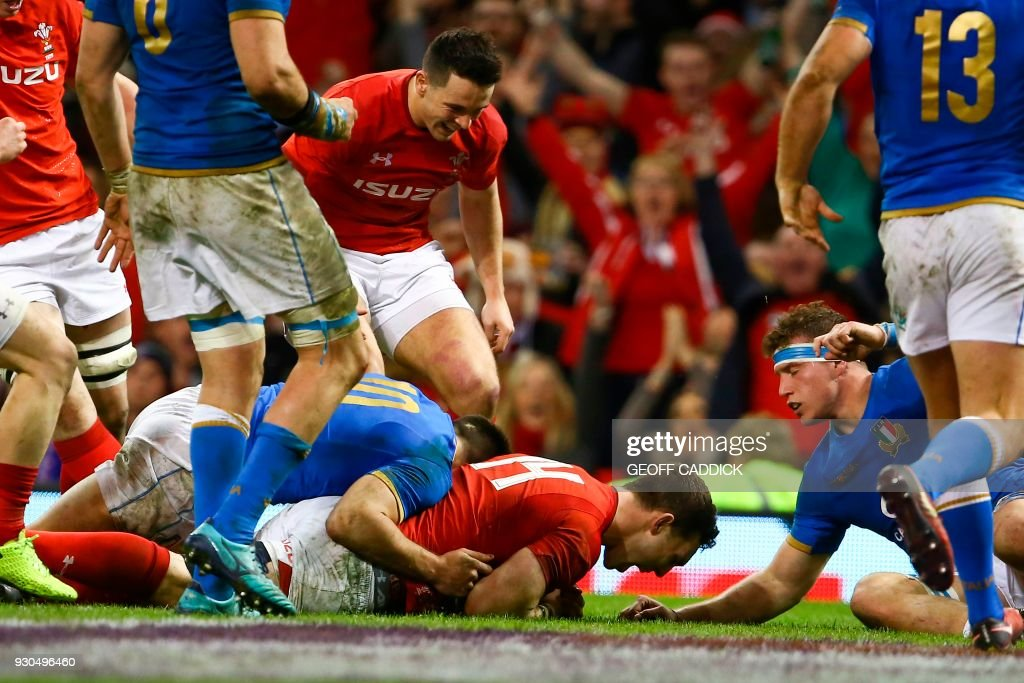 TOPSHOT - Wales' wing George North (C) scores a try during the Six Nations international rugby union match between Wales and Italy at the Principality Stadium in Cardiff, south Wales, on March 11, 2018. / AFP PHOTO / Geoff CADDICK / RESTRICTED TO EDITORIAL USE. Use in books subject to Welsh Rugby Union (WRU) approval.