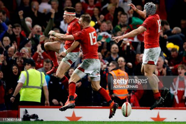 Wales' wing Josh Adams celebrates with Wales' fullback Liam Williams and Wales' centre Jonathan Davies after scoring the winning try during the Six...