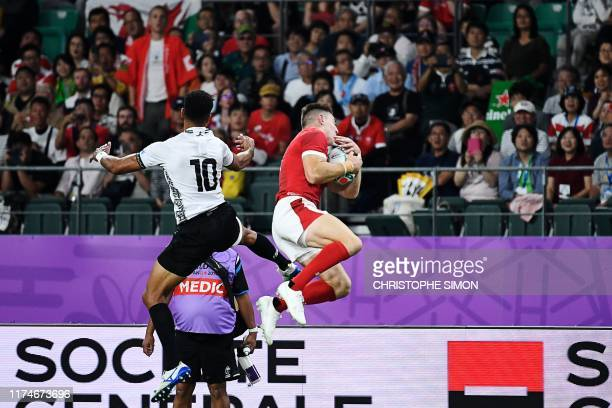 Wales' wing Joshua Adams and Fiji's flyhalf Ben Volavola jump for the ball during the Japan 2019 Rugby World Cup Pool D match between Wales and Fiji...