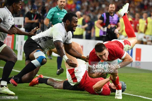 Wales' wing Joshua Adams scores a try past Fiji's scrumhalf Frank Lomani and Fiji's full back Kini Murimurivalu during the Japan 2019 Rugby World Cup...
