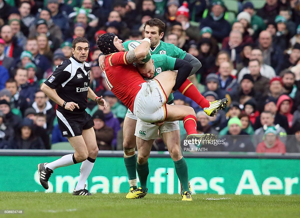 TOPSHOT - Wales' wing Tom James (C) is tackled by Ireland's wing Keith Earls during the Six Nations international rugby union match between Ireland and Wales at the Aviva Stadium in Dublin, Ireland, on February 7, 2016. / AFP / PAUL