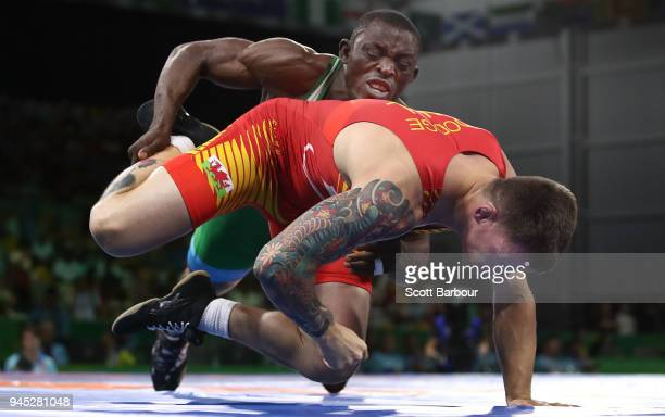 Wales's Curtis Dodge and Nigeria's Ebimienfaghe Assizecourt compete in the men's Freestyle 74Kg wrestling to win the Bronze medal during the...