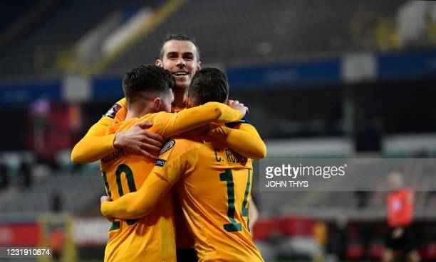 Wales's forward Harry Wilson celebrates with Wales' forward Gareth Bale and Wales' defender Connor Roberts after scoring a goal during the FIFA World...