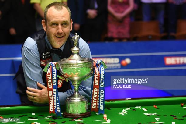 Wales's Mark Williams celebrates with the trophy after beating Scotland's John Higgins in the World Championship Snooker final match against at The...