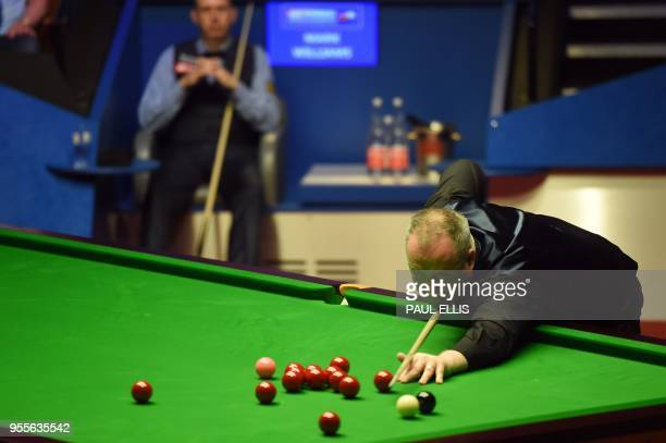 Wales's Mark Williams watches as Scotland's John Higgins plays a shot during their World Championship Snooker final match at The Crucible in...