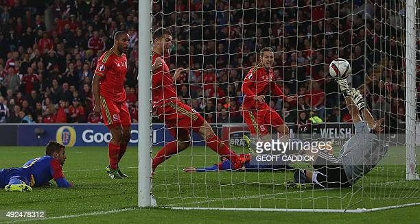 Wales's midfielder Aaron Ramsey watches the ball as he scores past Andorra's goalkeeper Ferran Pol Perez during the Euro 2016 qualifying football...