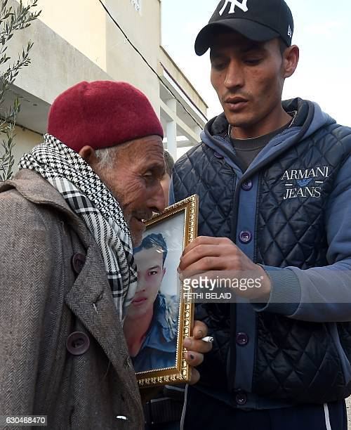 Walid Amri and Mustapha Amri the father and brother of 24yearold Anis Amri the prime suspect in Berlin's deadly truck attack hold a portrait of Anis...