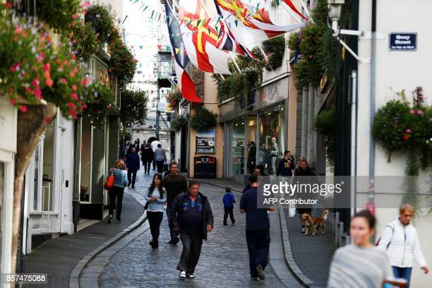 Walk along the high street on the island of Guernsey in the Channel Islands on October 3, 2017. / AFP PHOTO / CHARLY TRIBALLEAU