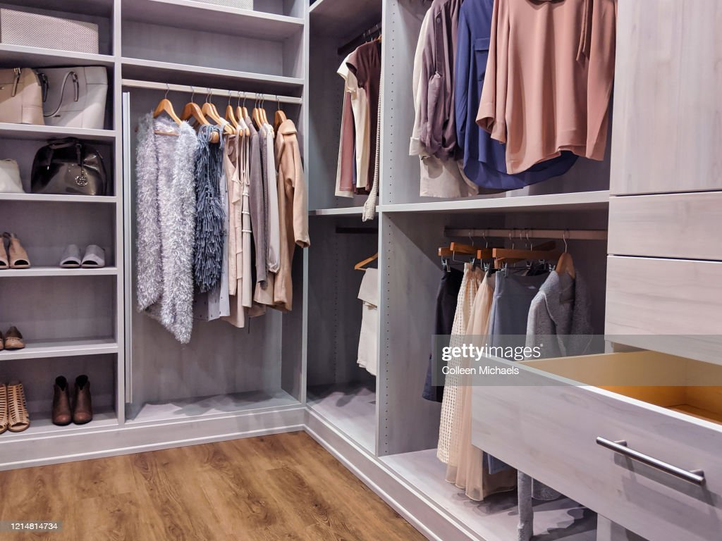 walk in closet with clothes hanging and shoes on shelving : Stock Photo