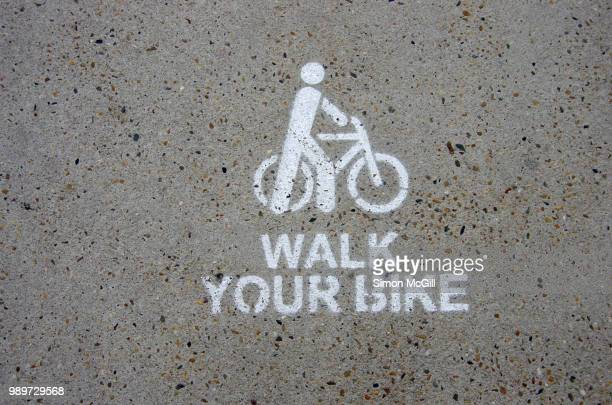 walk your bike sign stencilled on a concrete footpath - stencil stock pictures, royalty-free photos & images