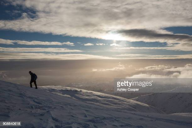 a walker ascending dollywagon pike in the lake district, uk. - deep snow stock pictures, royalty-free photos & images