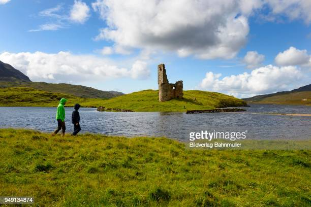 Walker at the ruins of the MacLeods of Assynt, Ardvreck Castle at Loch Assynt, Sutherland, Highlands, Scotland, Great Britain