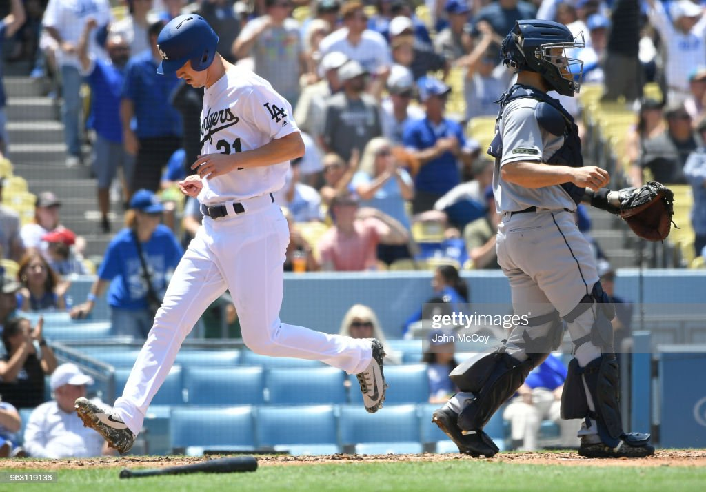 Walker Buehler #21 of the Los Angeles Dodgers crosses the plate behind Raffy Lopez #0 of the San Diego Padres to score a run in the third inning at Dodger Stadium on May 27, 2018 in Los Angeles, California.