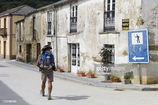 Walker checks sign on Camino de Santiago Pilgrim's Way to Santiago de Compostela at Triacastela in Galicia Spain