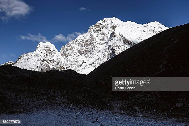 A walker dwarfed by the mountains surrounding Gorak Shep on September 30 2016 in Gorak Shep Nepal The trails in the SoluKhumbu region of Nepal are...