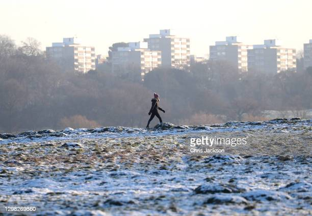 Walker makes their way through the remains of snowfall in Richmond Park on January 25, 2021 in London, England. Parts of the country saw snow and icy...