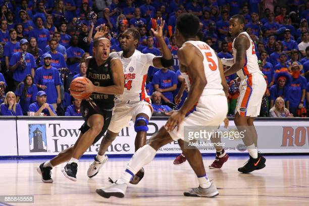 Walker of the Florida State Seminoles drives with the ball against Mak Krause and KeVaughn Allen of the Florida Gators during a NCAA basketball game...