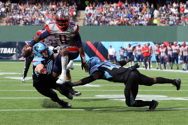 J Walker of the Houston Roughnecks leaps between Greer Martini of the Dallas Renegades and Tegray Scales of the Dallas Renegades for a threepoint...
