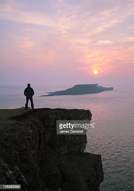Walker on the clifftops at Kitchen Corner looking out to sea towards Worms Head (Penrhyn-gwyr), at the southern end of Rhossili Bay at high tide, on the Gower peninsula in south Wales