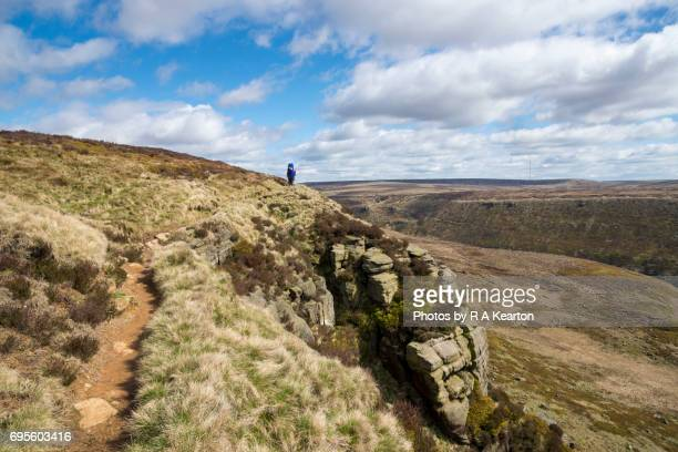 Walker on the Pennine way footpath, Northern England