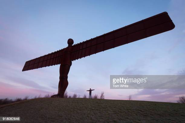 A walker poses next to the Angel of the North at sunrise on February 14 2018 in Gateshead England Tomorrow marks the 20th anniversary since the...
