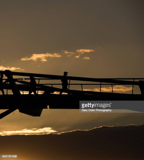 walker silhouetted on millennium bridge - gary colet stock pictures, royalty-free photos & images