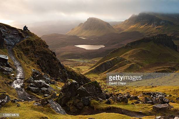 Walker sits on a viewpoint at The Quiraing, a twenty four mile rock ledge on the Isle of Skye, Scotland, UK