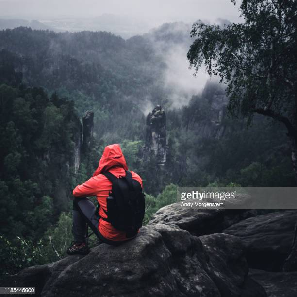 walker sitting on rocks at a rainy day - red jacket stock pictures, royalty-free photos & images