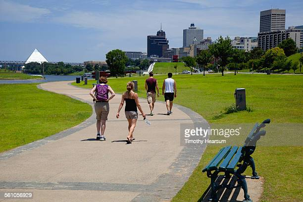 walkers along river with city beyond - memphis tennessee stock pictures, royalty-free photos & images
