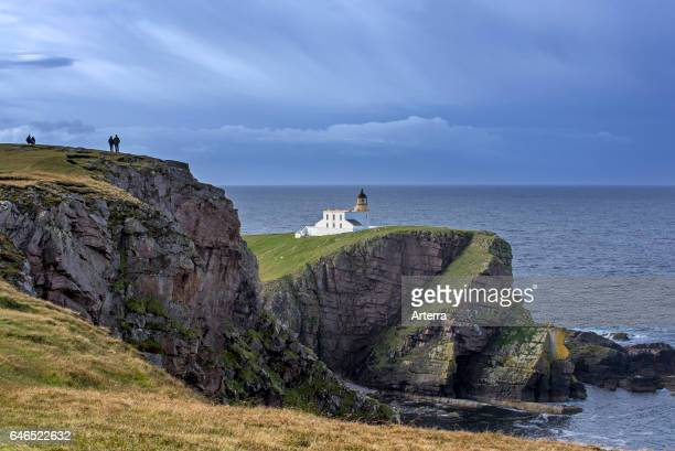 Walkers and the Stoer Head Lighthouse at the Point of Stoer in Sutherland Scottish Highlands Scotland UK