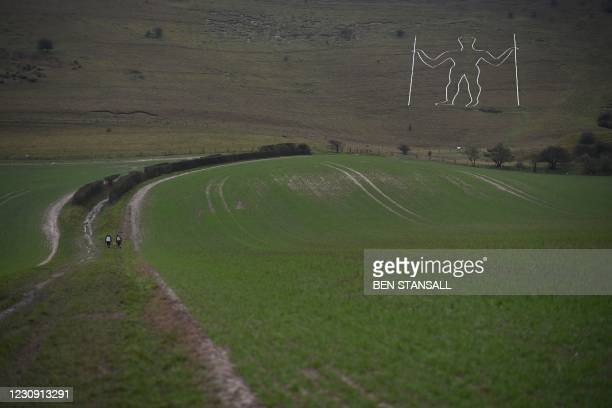 Walkers approach the Long Man of Wilmington carved into the hillside near Eastbourne on southern England on February 1, 2021. - Vandals had painted a...