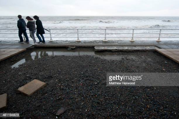 Walkers avoid a large hole in the pavement caused by strong waves hitting the promenade on January 7, 2014 in Aberystwyth, Wales, United Kingdom. A...