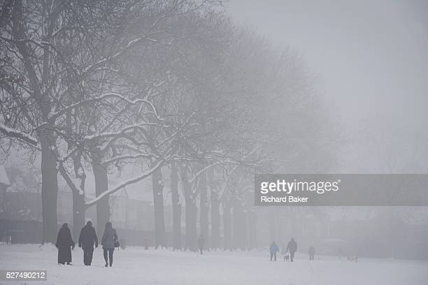 Walkers brave freezing temperatures in their local London park During a prolonged cold spell of bad weather snow fell continuously on the capital...