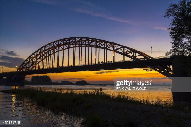 Walkers cross the Waalbrug river during sunrise on the first day of the 98th annual fourdays walking event 'the Vierdaagse' on July 15 2014 in...