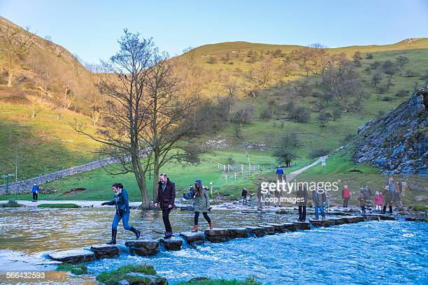 Walkers crossing the stepping stones in Dovedale