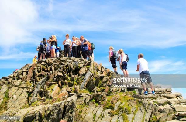 Walkers crowd onto the summit point, Mount Snowdon, Gwynedd, Snowdonia, north Wales, UK.