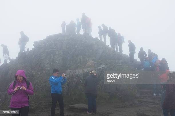 walkers in the mist at the summit of mount snowdon - mount snowdon stock photos and pictures