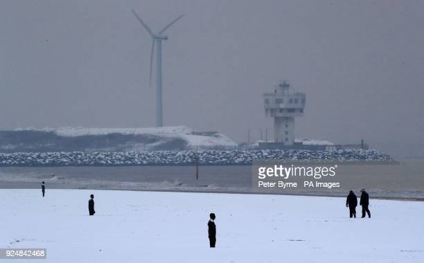 Walkers in the snow near to Another Place by Anthony Gormley on Crosby Beech near Liverpool following heavy overnight snowfall which has caused...