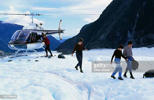 Walkers leaving helicopter on glacier.