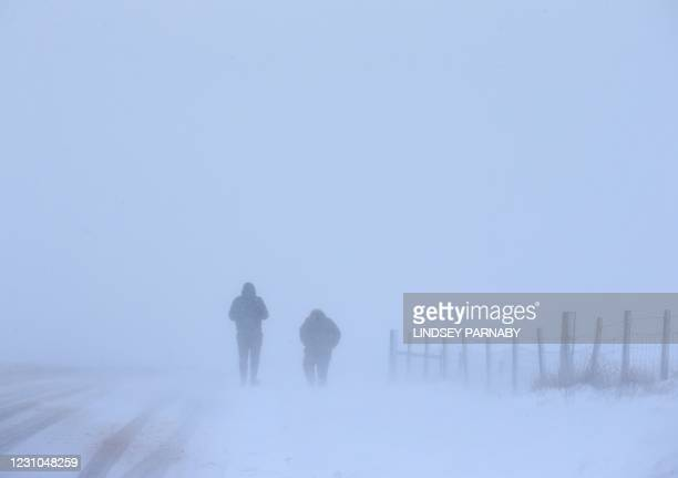 Walkers make their way through the snow during a blizzard-like conditions in Saddleworth, northern England on February 8, 2021. - Cold weather swept...